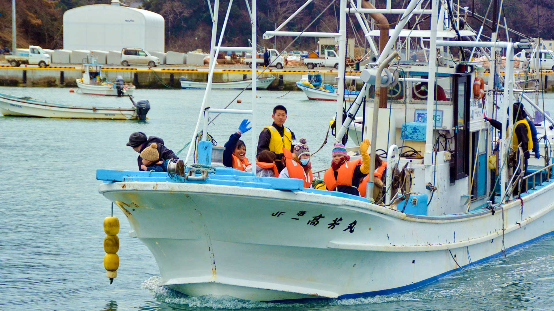 漁船から手を振る学生
